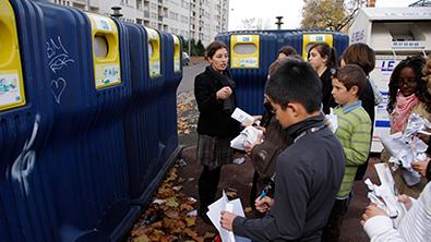 Un groupe d'enfant devant des conteneurs de recyclage, une guide est en train de leur parler