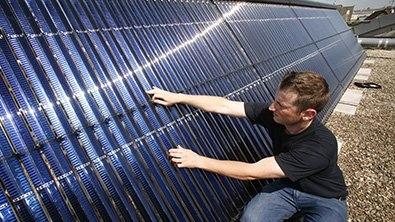 Un homme vérifie une grande surface de panneaux solaires